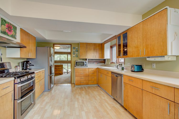 mid century modern kitchen with stainless steel appliances white countertops oak cabinets