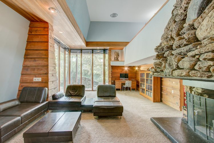 mid century modern living room with stone fireplace and floor to ceiling windows frank lloyd wright inspired