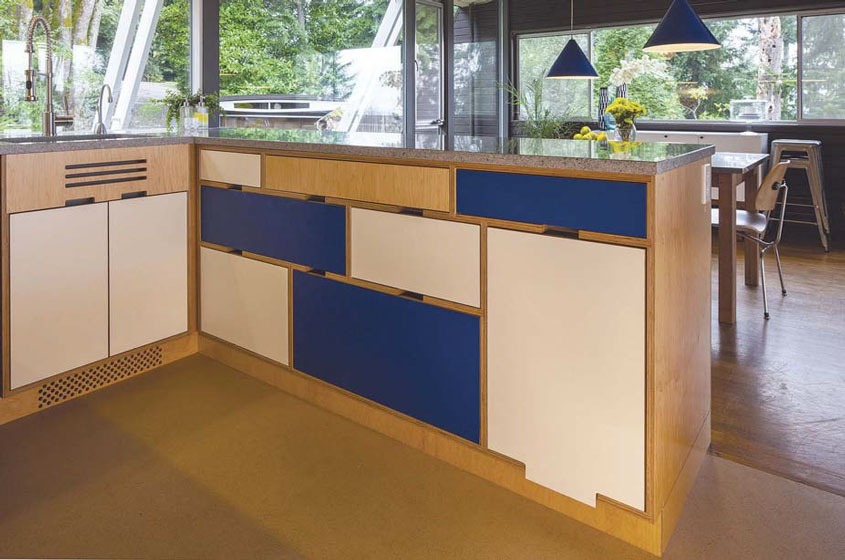 The three drawer refrigerators and freezer unit formatted into a finished-plywood island with white and blue laminate drawers.