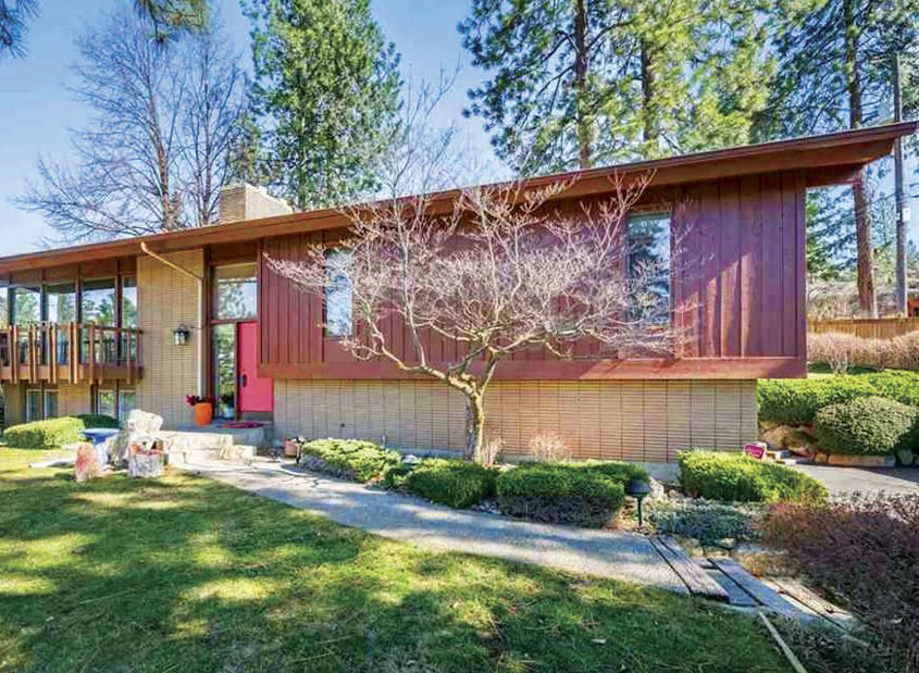 The exterior of an MCM home in Spokane, Washington complete with a red door, ribbed exterior, and price that is all too perfect.