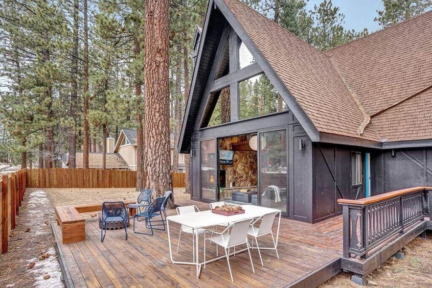 An outer view of the A-frame cabin showcasing the extended deck and paneled window facade.