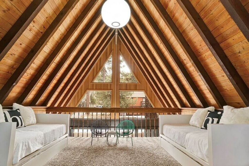 The loft area of the A-frame cabin, focusing specifically on the architecture and modern arrangements.