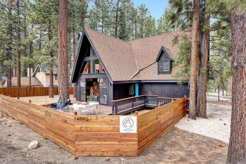 A back view of the A-frame cabin, showcasing its sliding glass doors, black exterior, chestnut-colored roof and deck.