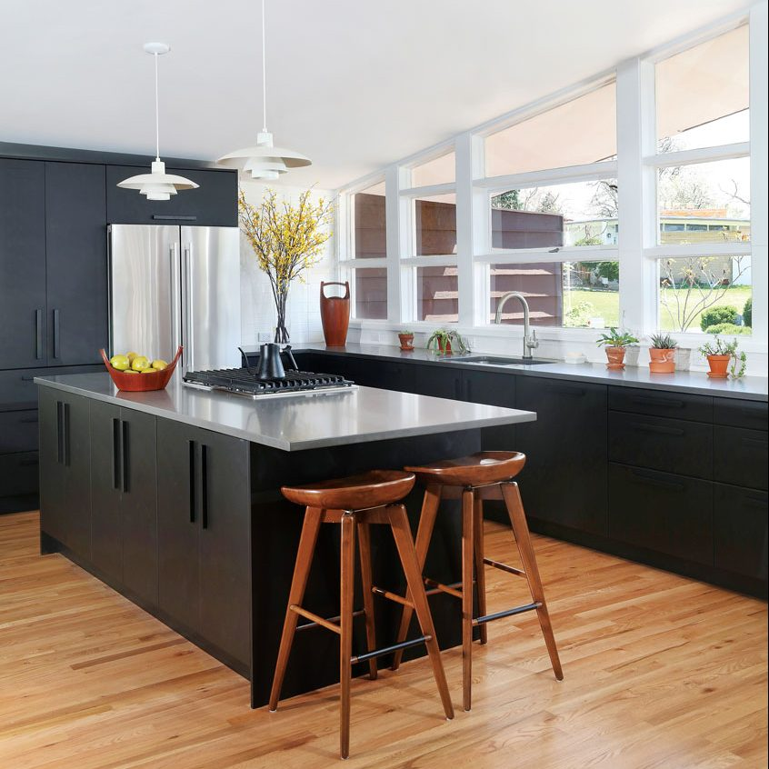 This kitchen upgrade showcases a black and wooden design scheme with a central island.
