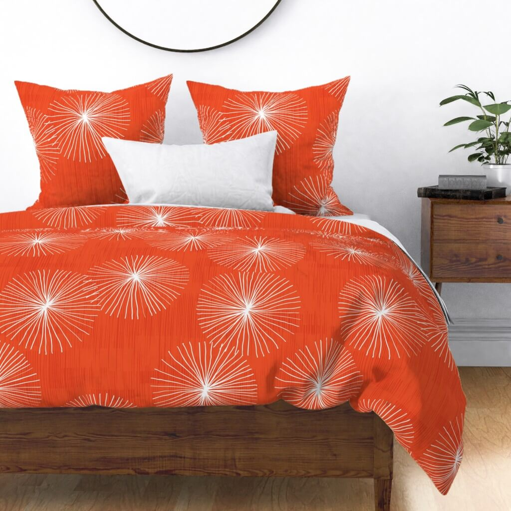 Red mid century bedding complete with a white dandelion that surrounds the exterior.