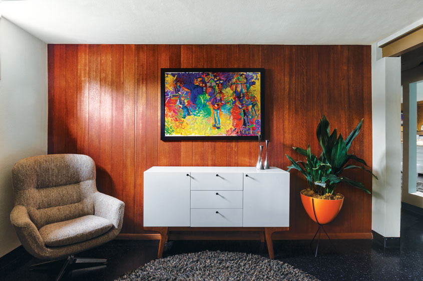 The basement of this mid century home with a mahogany wood wall scheme, white credenza, and orange bullet planter.