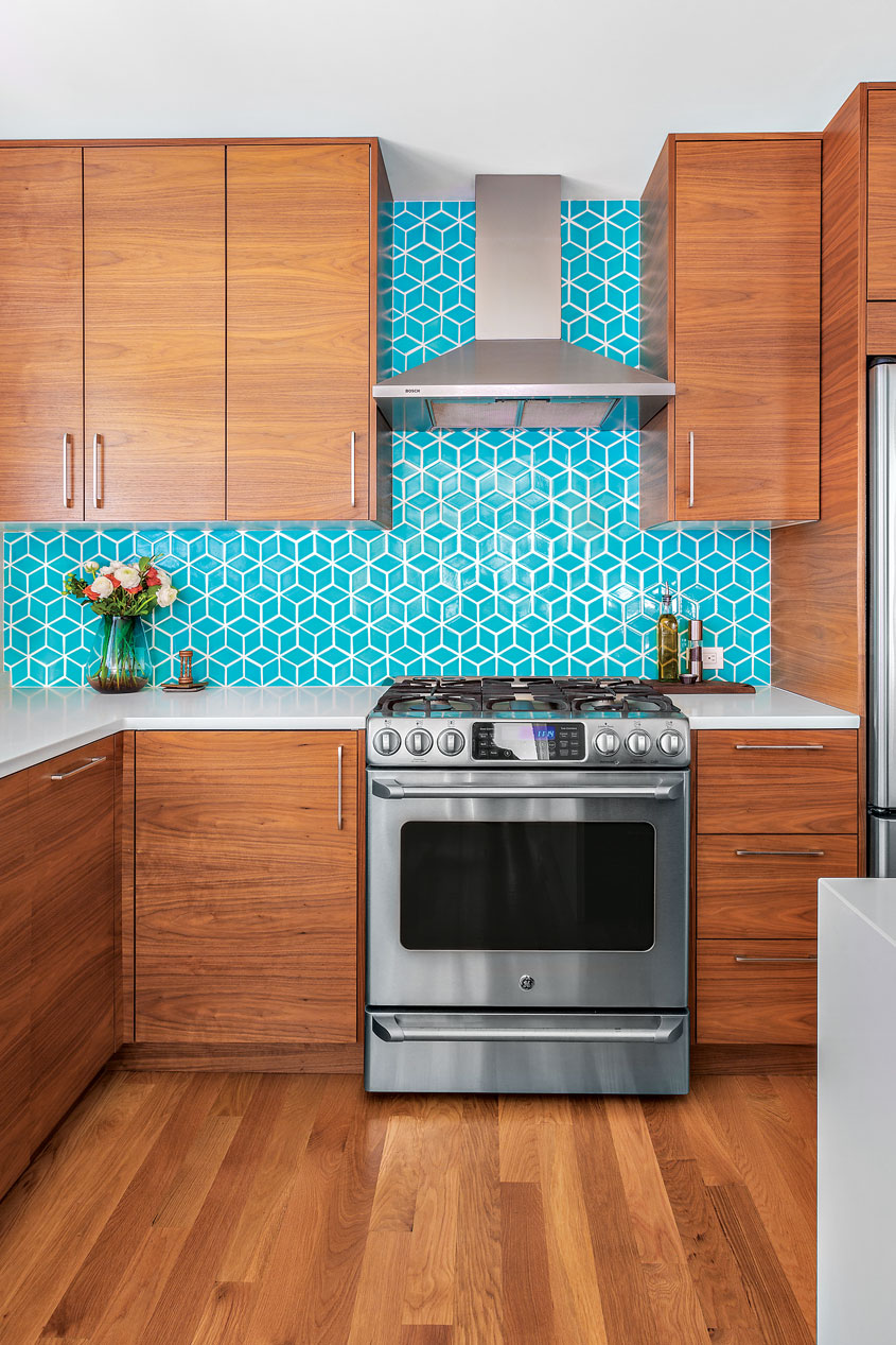 A kitchen complete with cubed turquoise wall tiles, walnut cabinets, white countertops, and a stainless steel oven.