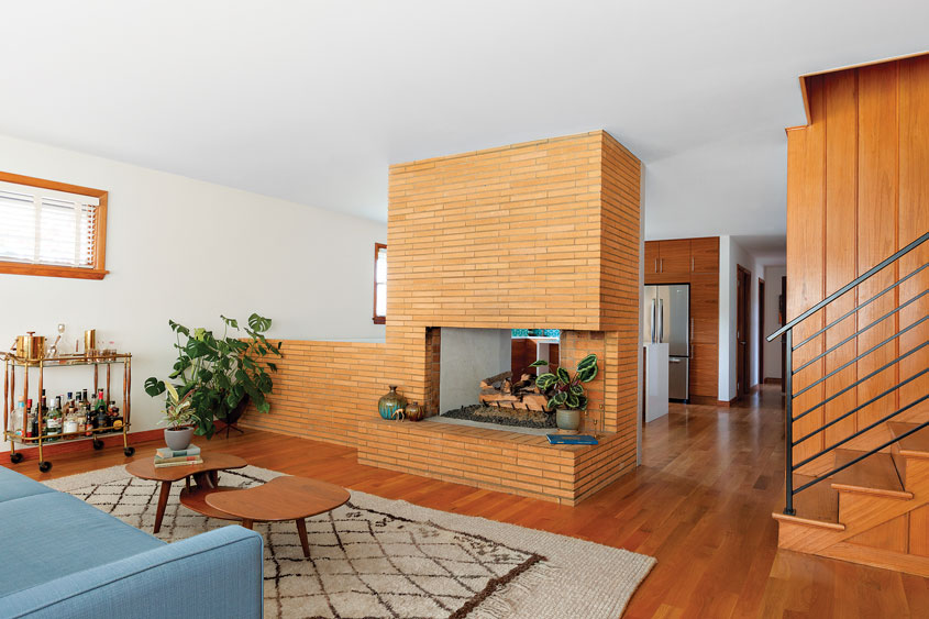 A brick fireplace separating the living room and kitchen of this Portland puzzle.