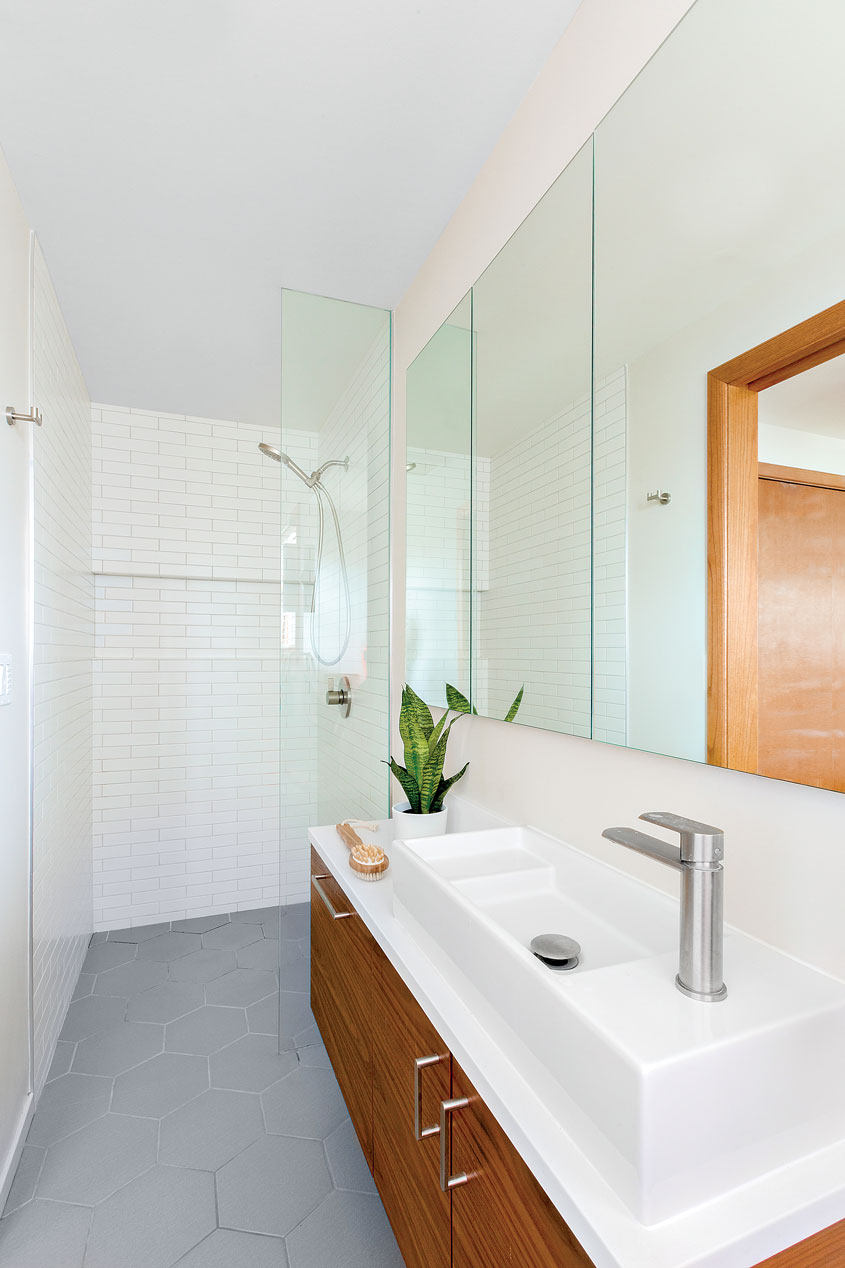 A bathroom with a white interior, shower at the end of the corridor, and large mirrors in this Portland puzzle.
