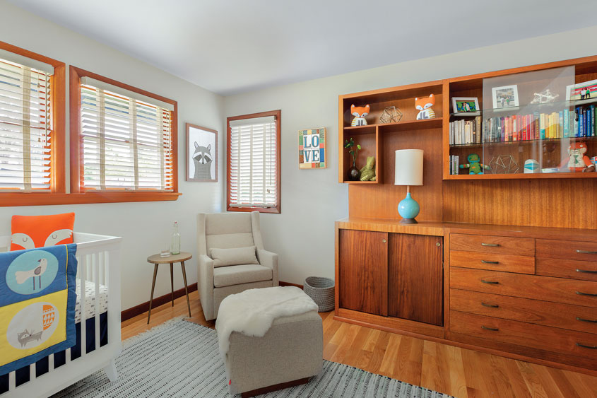 A mid century nursery room complete with mahogany floors and minimalistic infant decor as a part of this Portland puzzle.