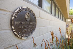 A plaque on the exterior wall of a house shows the home's historical designation by the city of San Diego due to the home's famed designer, Lloyd Ruocco.