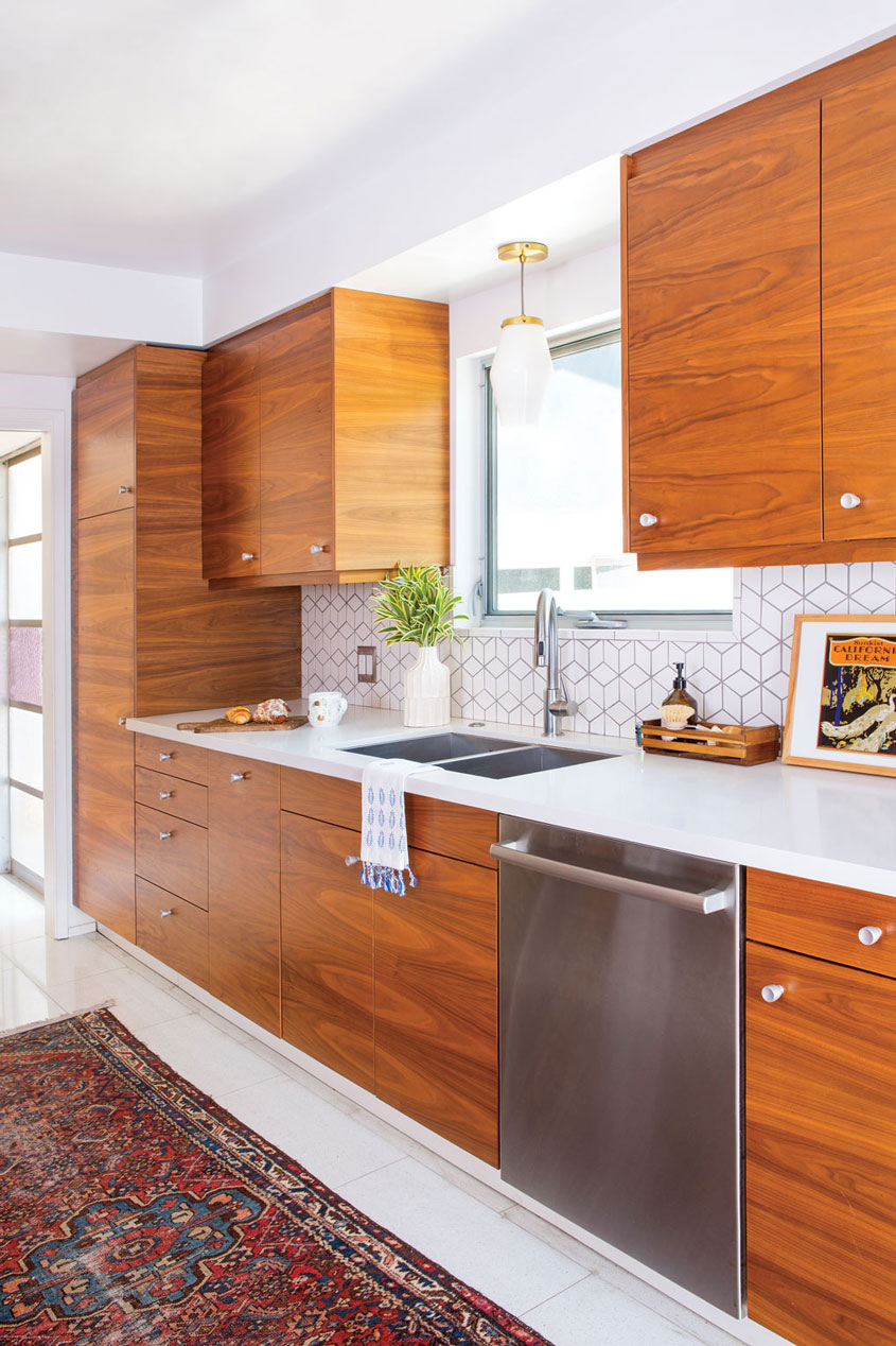 A custom design kitchen with walnut cabinets and a white tabletop scheme.