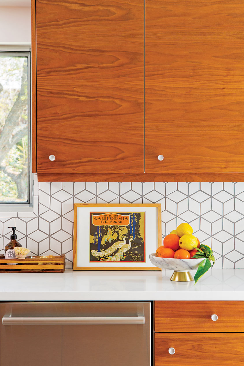 The kitchen's custom wood cabinets and white cubed wall tiles.