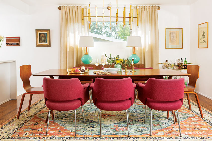 The custom design dining room complete with a wooden table and maroon chairs overlooking a large window.