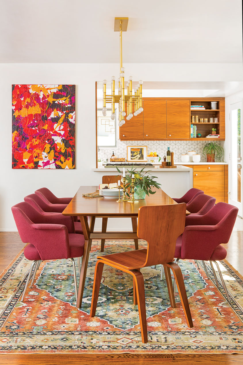 The custom design dining room showcasing a wood table and maroon chairs that is ultimately connected to the kitchen.