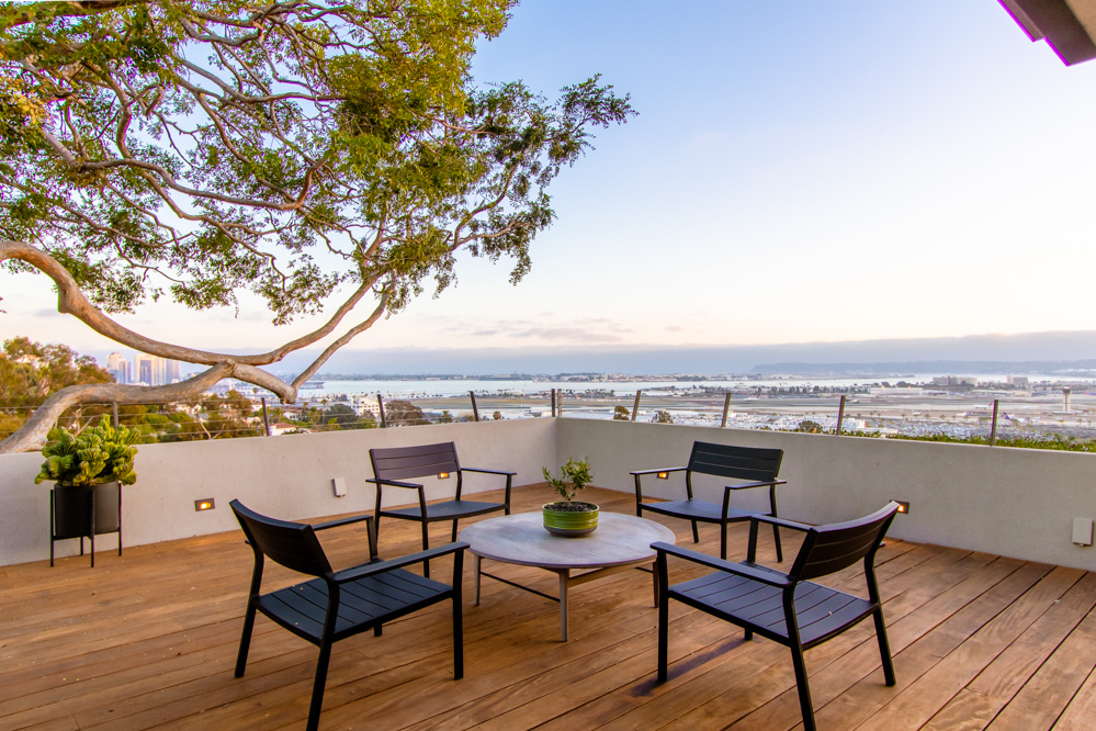 A large deck with outdoor furniture overlooks the San Diego Bay, with Chinese elms framing the view.