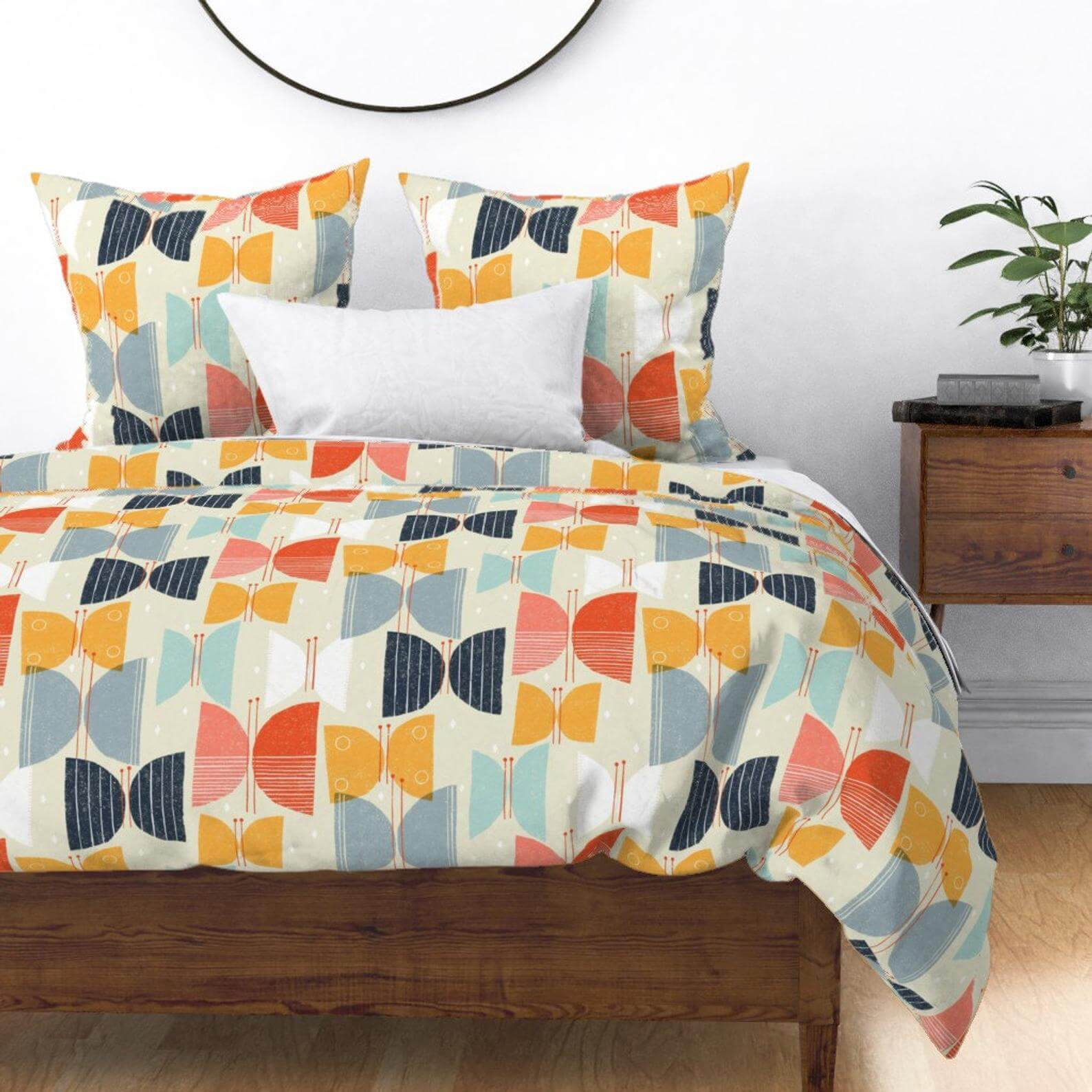 Mid century bedding covered in an abstract multi-colored butterfly pattern.