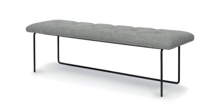 A bench with an intricate leg scheme and a gray cushion.