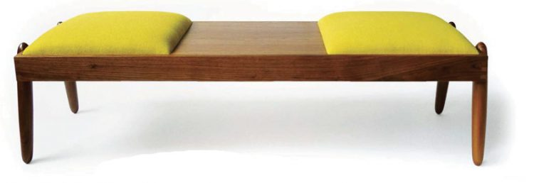 A mid century bench with a polished-wood exterior and two yellow cushions on each side.