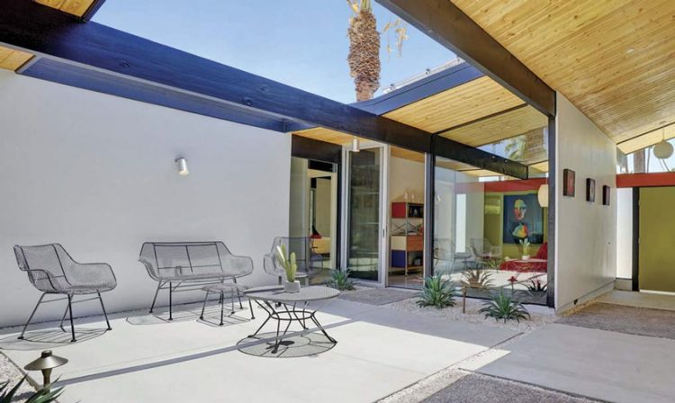 A mid century backyard featuring an open atrium and geometrically placed plants.