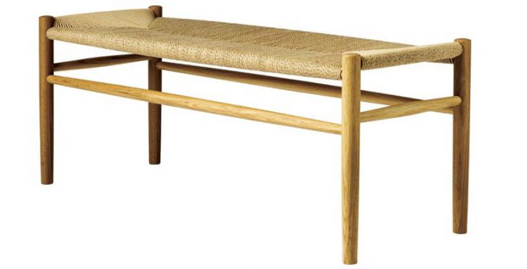 A mid century bench with a wood-weaved exterior.