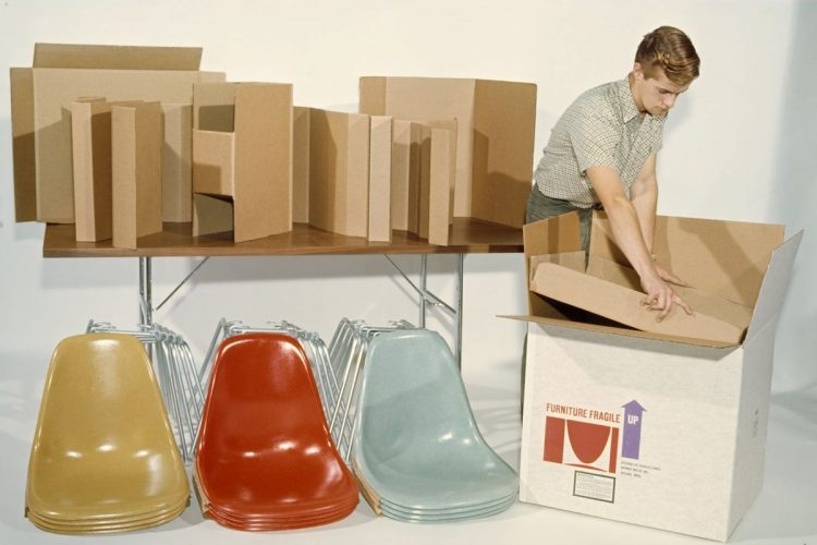 A man unpacking a slew of red, blue, and yellow Eames chairs to emphasize Adam Call's take on Herman Miller.