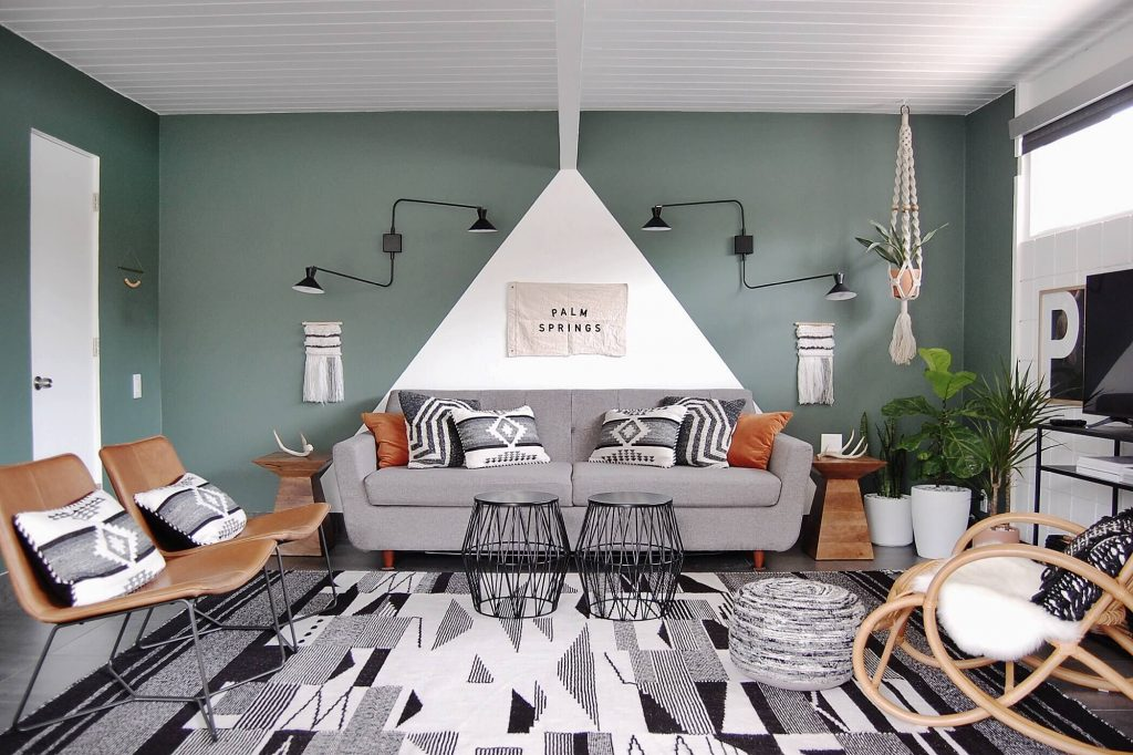 A mid century living room that features a geometrically-set rug, as well as a gray and teal color scheme.