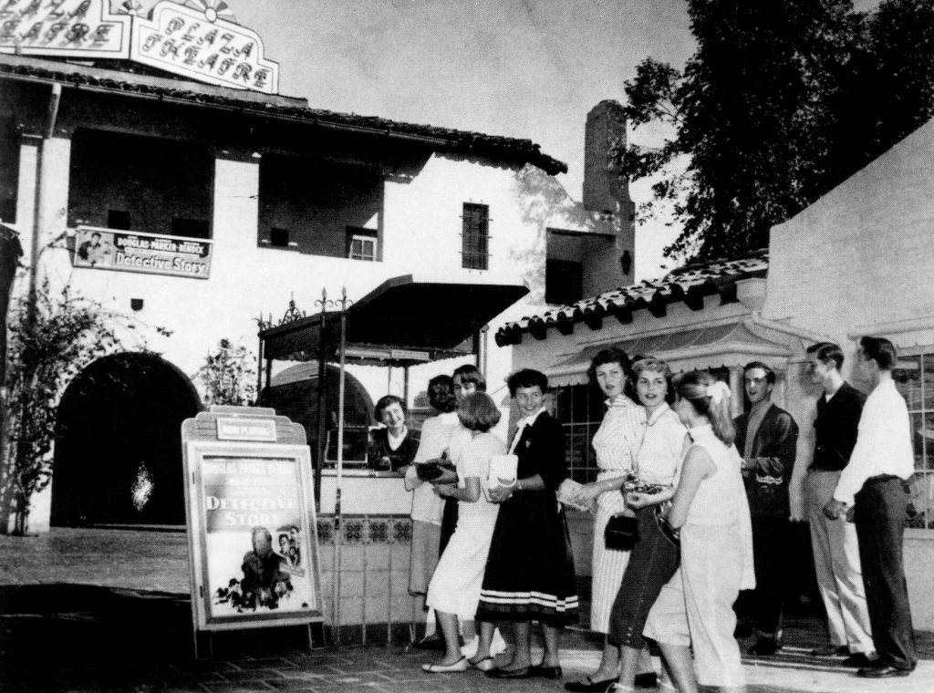A black and white photograph of people lined up at the plaza theatre looking back toward the camera.