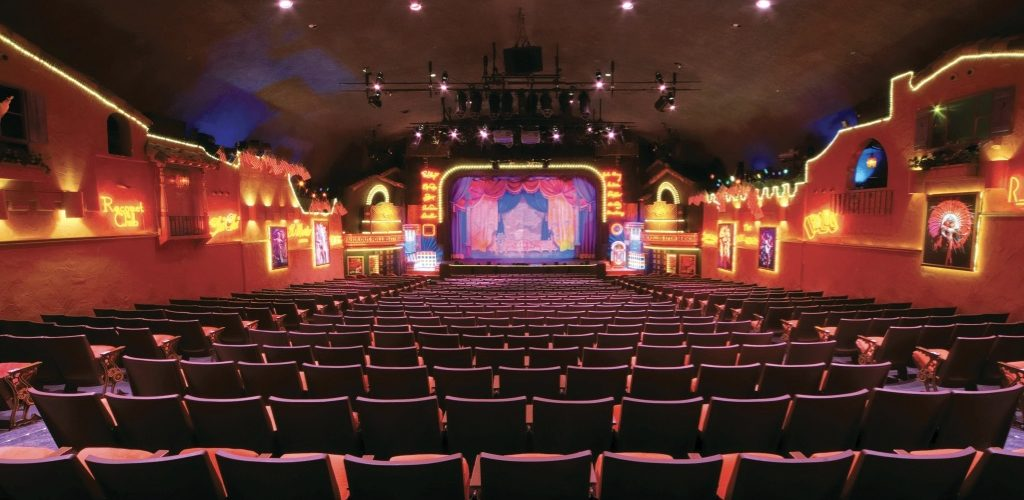 The plaza theatre interior detailing its red chairs and expansive hall.