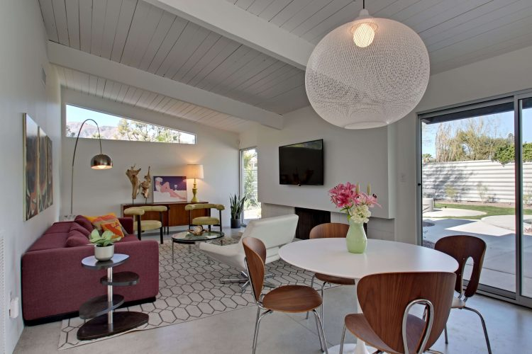A mid century living room with a slanted white ceiling and an array of sleek mid century pieces.