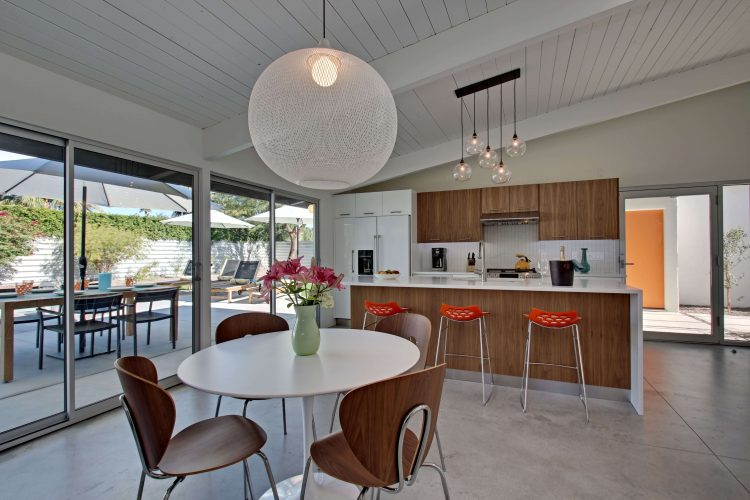 A mid century kitchen makeover with an orb light fixture, single table, and island seating.