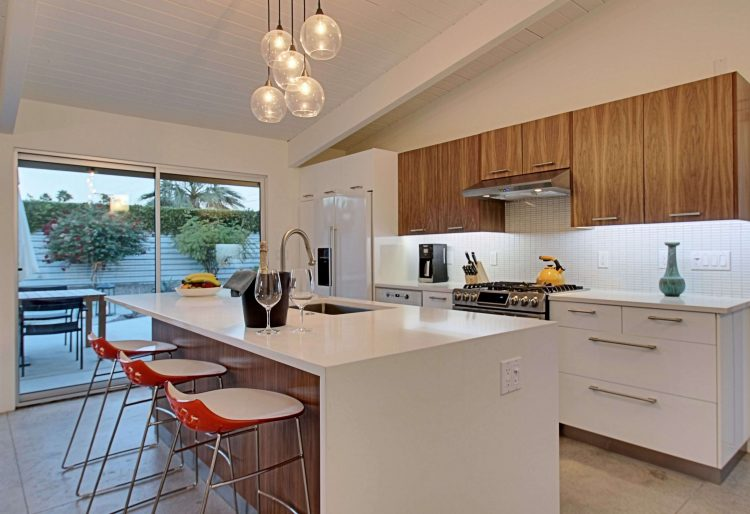 A mid century kitchen makeover with a long island, orange dining stools, and wood cabinetry.