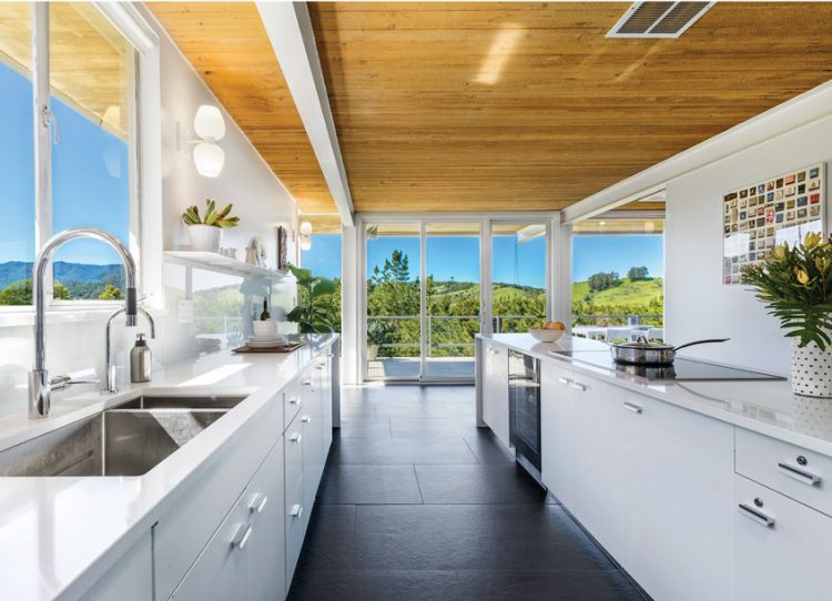 The kitchen's modular design in Case Study House #26, showcasing its tile floors and white cabinets.