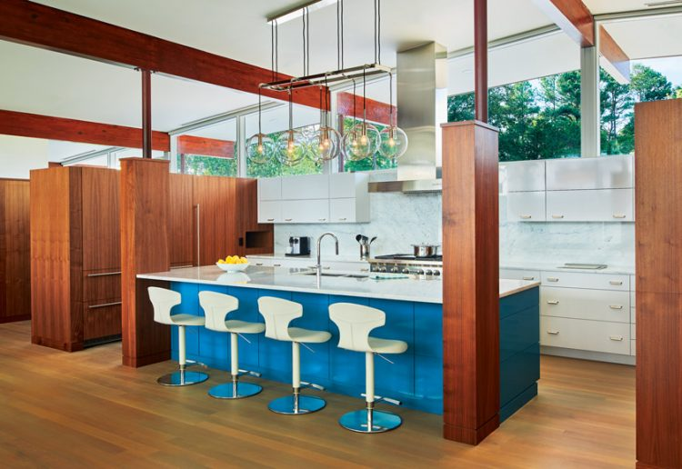 A mid century modern remodeled home featuring a kitchen with a blue island and corresponding bar stools.