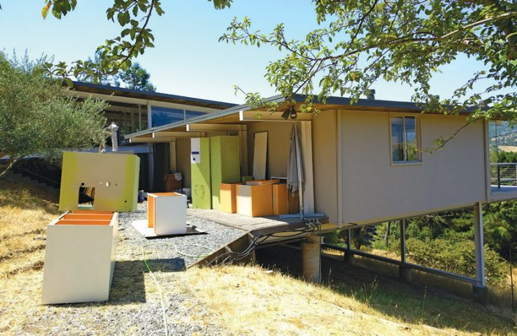 A Case Study House by the budget with internal appliances being worked on from the home's exterior.