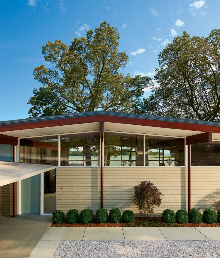 The exterior of a home that just underwent a mid century makeover, displaying its clerestory roof design.