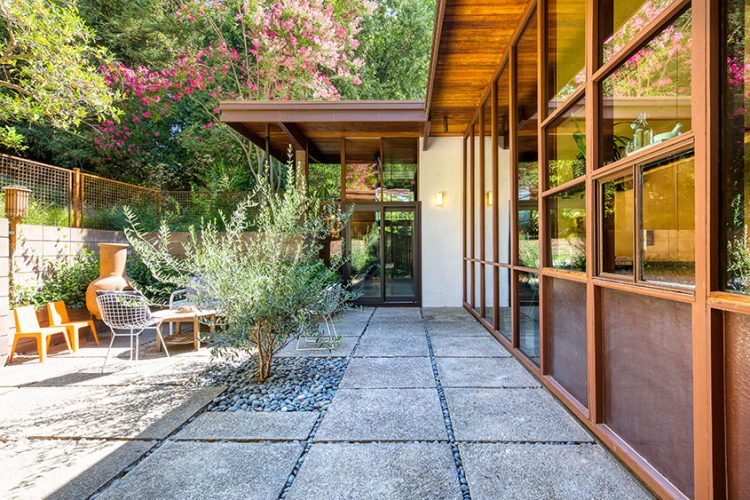 A personalized mid century modern patio with a distinct concrete walkway.