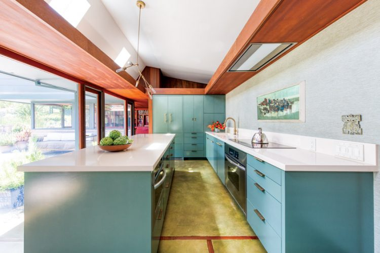 A mid mod kitchen with floor to ceiling glass walls, a large island, and teal cabinetry.