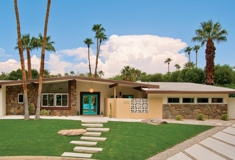 A mid century front yard featuring a blue front door stone walkway.