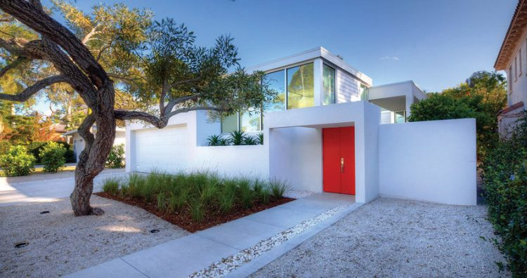 The exterior of a mid mod home with a bright red door and geometric house structure.