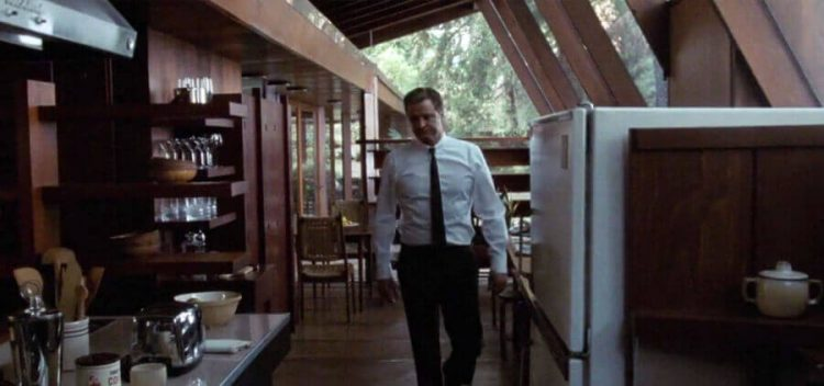 Mid century movie with man walking through kitchen.
