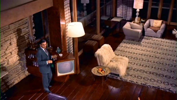 Mid century modern movie with a man standing in living room next to white chair.