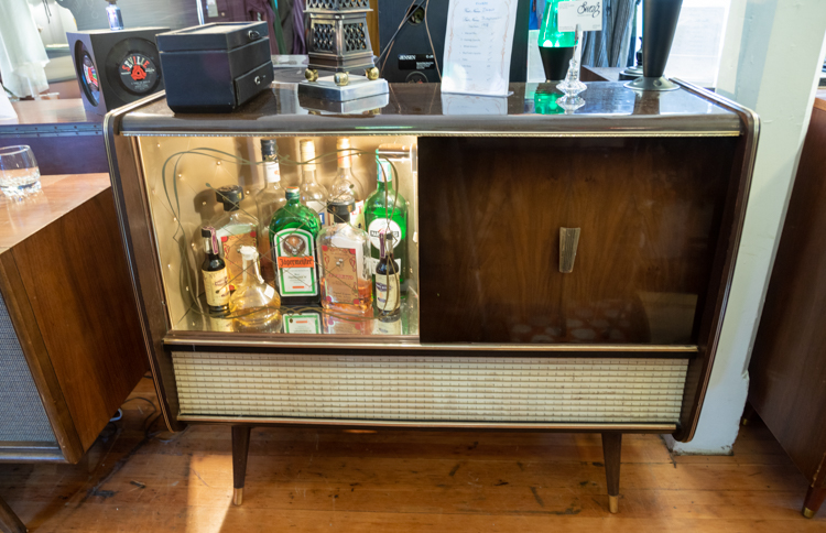 A mid century stereo console with half used as a bar