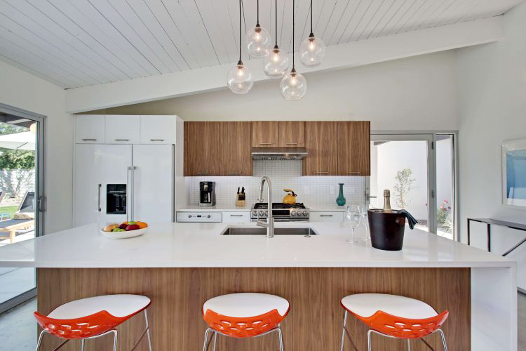 A mid century kitchen makeover with a dangling pendant light, orange dining stools, and white countertops.