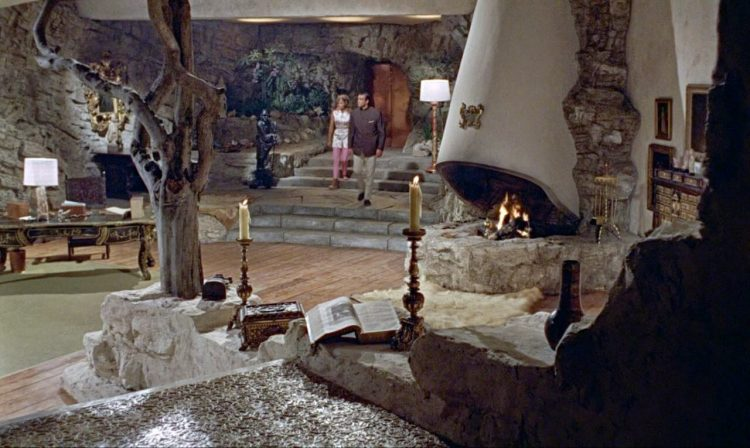 Mid century movie home with natural wood and rock detailing and a large hooded fireplace.