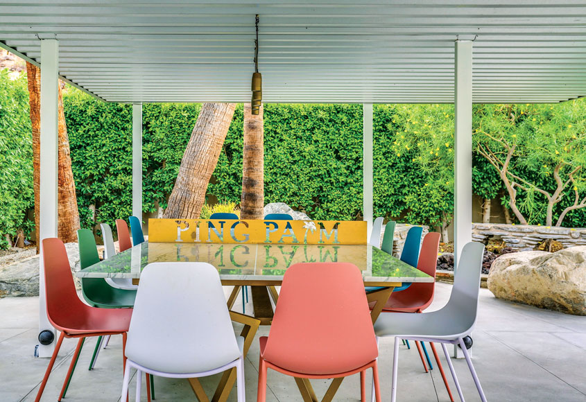 An outdoor dining area with a mix of colorful shell chairs around a shiny topped table