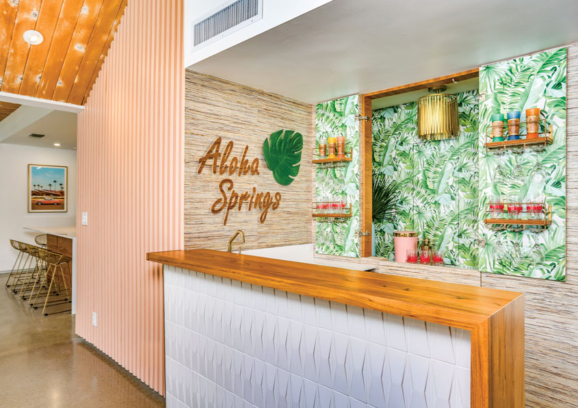 "Lindsey added the wood paneling seen here and painted it coral. She also turned an alcove into a hideaway bar with both sophisticated seagrass and ""instant party mode"" wallpaper."