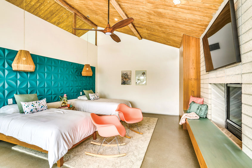 a guest room with two double beds, a pair of pink molded Eames rockers and three-dimensional deep turquoise walls behind the beds which serve as headboards. Above each bed are modern rattan light pendants.
