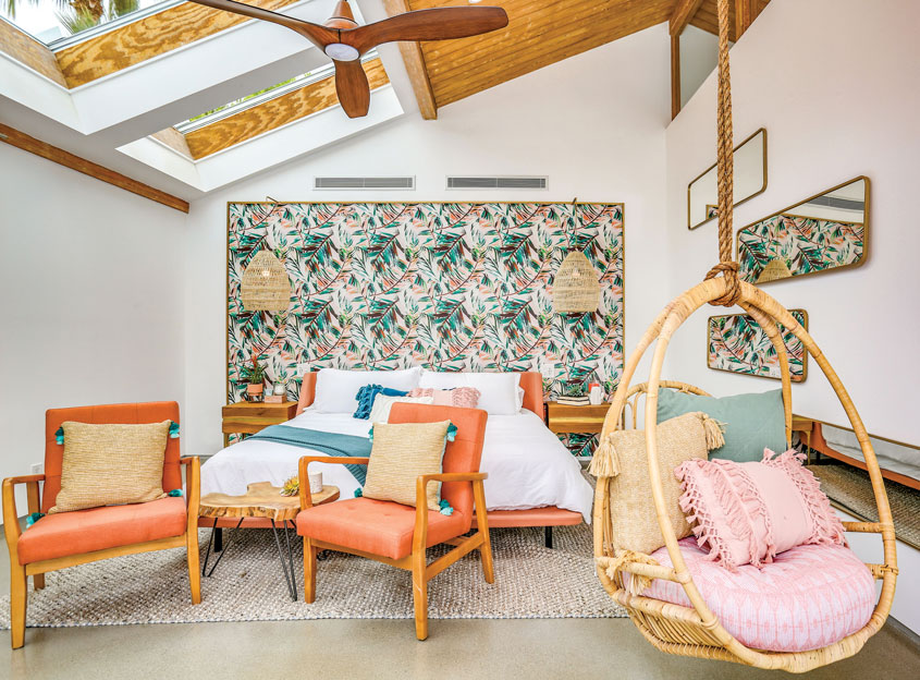 A master bedroom in an Alohaus Swiss Miss home. The bed is backed by a wallpaper focal wall which also serves as a headboard. A hanging rattan egg chair adds a fun tropical vibe.