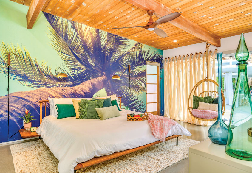 Palm-print wallpaper, natural-fiber and teak accents, as well as sunset-hued upholstered furnishings, tie together this tropical oasis.